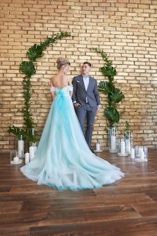 Świeżo poślubiona para, kochająca się para przed ślubem. kochający się mężczyzna i kobieta. panna młoda w turkusowej sukience i pan młody w niebieskim garniturze. dekoracje ślubne, strefa zdjęć ślubnych