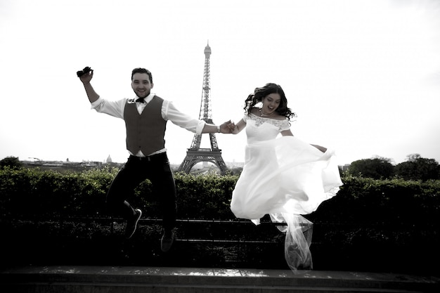 Świeżo poślubiona para w paryżu, w pobliżu wieży eiffla