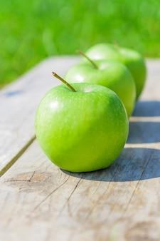 Świeżo przycięte zielone jabłka na drewnianym stole nad zieloną trawą