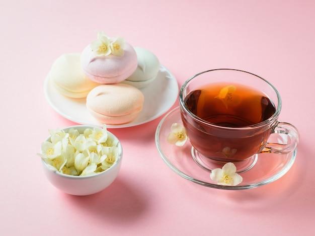 Świeżo przygotowana herbata i kolorowe pianki na różowym stole. skład porannego śniadania.