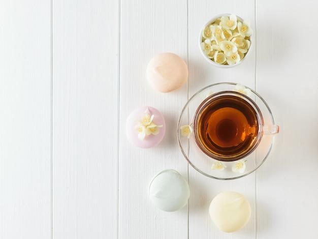 Świeżo przygotowana herbata i trzy kolorowe pianki na białym drewnianym stole