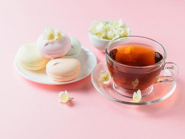 Świeżo przygotowana herbata, kolorowe pianki i jaśmin na różowym stole. skład porannego śniadania.