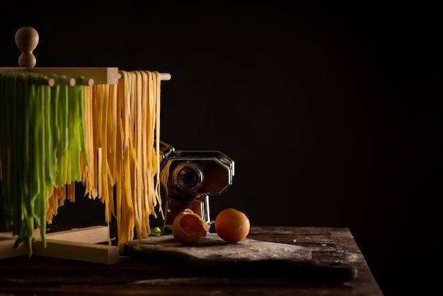 Świeżo przygotowana pasta tagliatelle jest suszona na drewnianej suszarce, tradycyjnej kuchni włoskiej