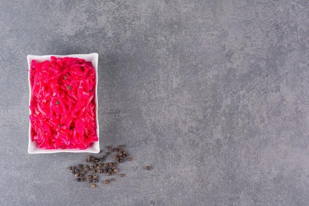 Świeżo przygotowana porcja czerwonego coleslaw postawiona na kamiennym stole.