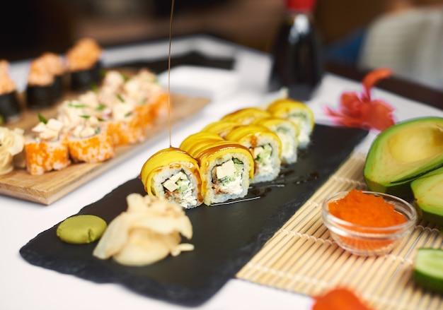 Świeżo przygotowana rolka sushi polana sosem teriyaki.