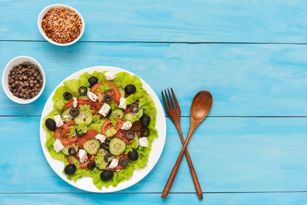 Świeżo przygotowana sałatka grecka z serem feta i różnymi przyprawami.
