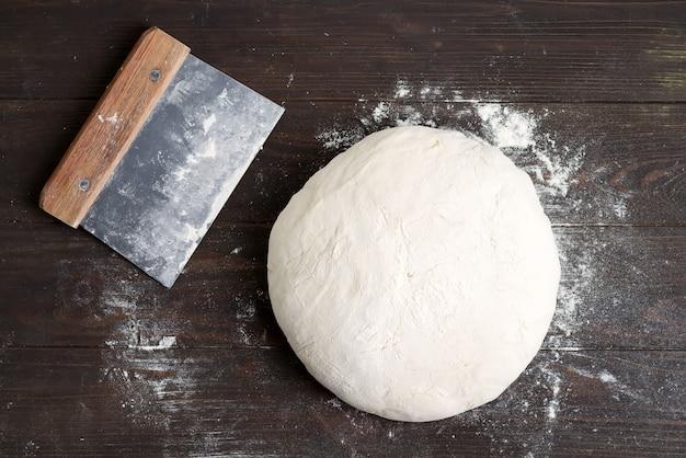 Świeżo przygotowane ciasto drożdżowe dla zdrowia domowego chleba na podłoże brązowe drewniane tła.