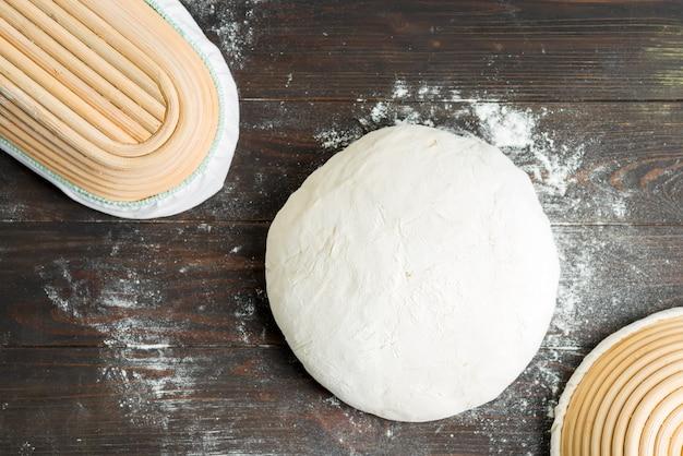 Świeżo przygotowany bochenek domowej roboty białego zdrowego chleba i ciasta kosz jest gotowy do pieczenia na ciemnym drewnie, miejsce. widok z góry.