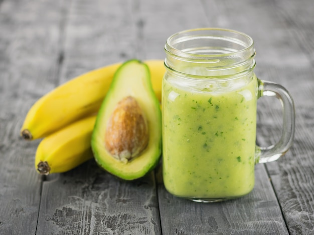Świeżo przygotowany koktajl z awokado, banana, pomarańczy, cytryny, pietruszki i kiwi na drewnianym stole. dieta wegetariańska.