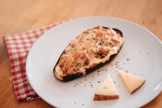 Świeżo przyrządzone danie z bakłażana faszerowanego wołowiną, serem, beszamelem i przyprawami np. oregano