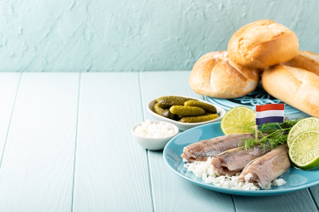 Świeżo solony śledź, tradycyjny holenderski przysmak zwany hollandse nieuwe na turkusowym talerzu i drewnianej powierzchni. europejska koncepcja żywności z miejsca na kopię