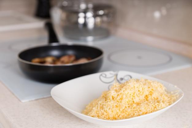 Świeżo starty ser cheddar w misce stojącej na kuchennym blacie obok smażenia mięsa na płycie grzejnej czeka na dodanie do przepisu