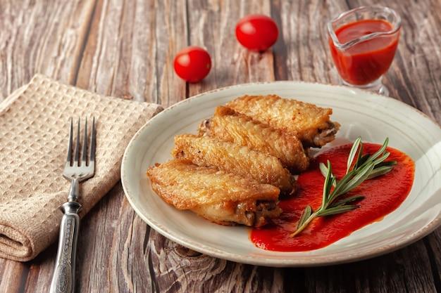 Świeżo ugotowane buffalo wings zbliżenie z sosem pomidorowym i pomidorami