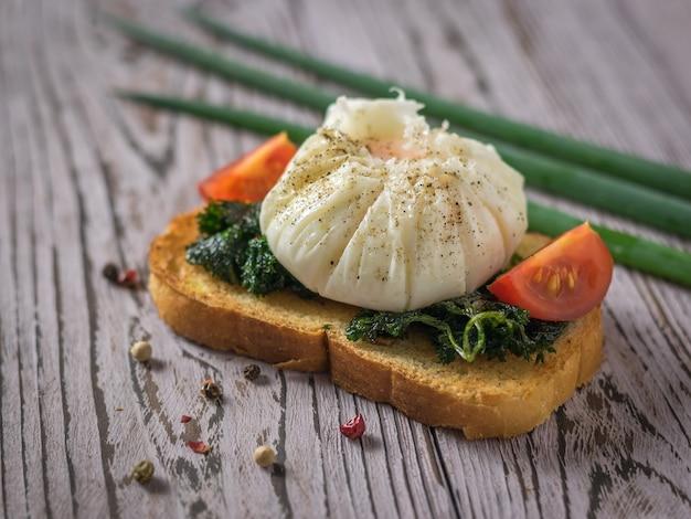 Świeżo ugotowane jajko na kawałku chleba tostowego z pomidorem i ziołami. wegetariańska przekąska z jajkiem w koszulce.