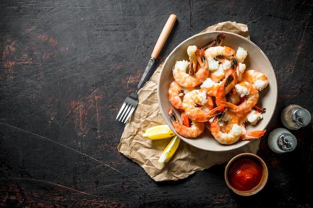 Świeżo ugotowane krewetki z przyprawami, sosem i cytryną na ciemnym drewnianym stole