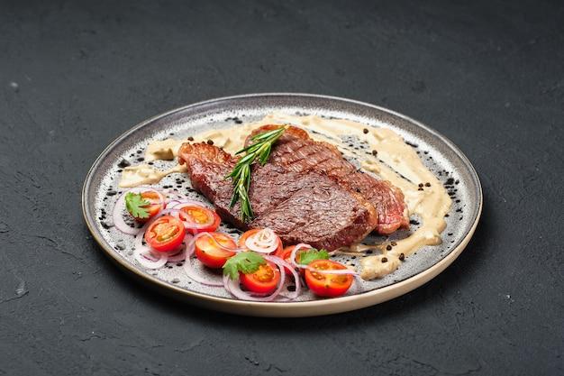 Świeżo ugotowane mięso na metalowym talerzu pomidor w plasterkach