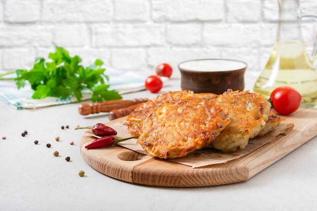Świeżo ugotowane placki ziemniaczane ze śmietaną na drewnianej desce na kuchennym stole. danie wegetariańskie