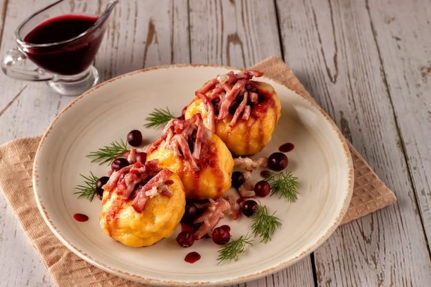 Świeżo ugotowane szwedzkie knedle ziemniaczane z sosem żurawinowym na jasnym tle.