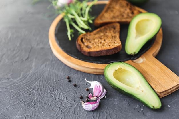 Świeżo ugotowane tosty z pełnego ziarna z awokado i drobnozielonymi kiełkami