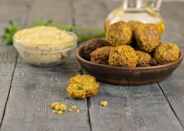 Świeżo ugotowany falafel na glinianej misce na drewnianym stole z sosem tahini i natką pietruszki