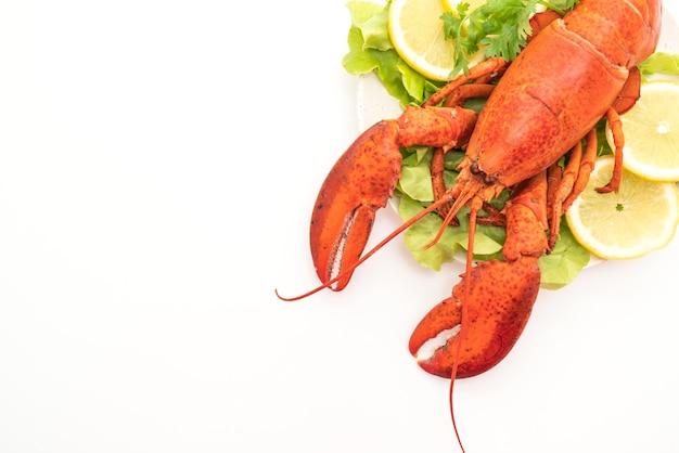 Świeżo ugotowany homar z warzywami i cytryną na białym tle