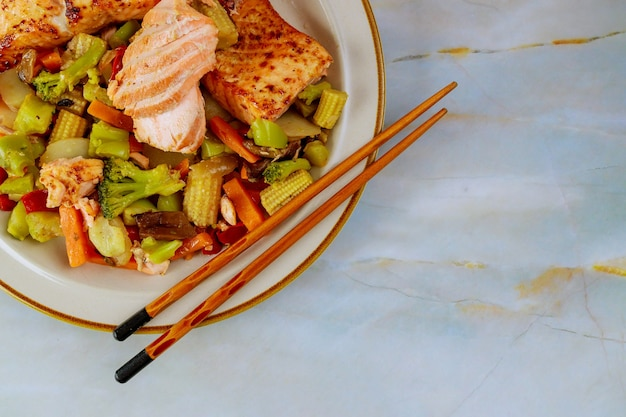 Świeżo ugotowany łosoś na talerzu z sałatką i cytryną na białym stole.