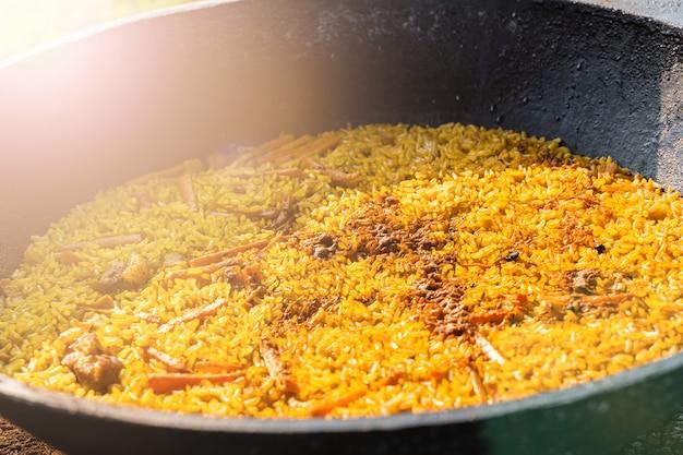 Świeżo ugotowany pilaw w dużym metalowym kociołku. pyszne doskonałe jedzenie. kuchnia narodowa uzbekistanu.