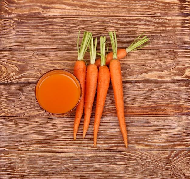 Świeżo umyte całe marchewki na starym drewnianym stole