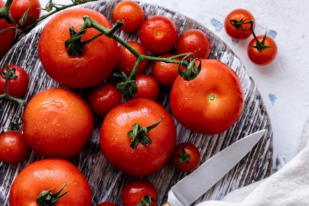 Świeżo umyte pomidory na desce do krojenia