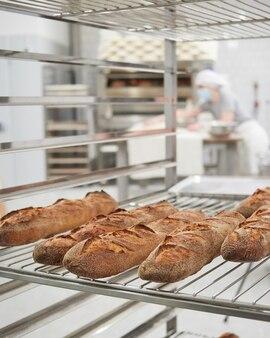 Świeżo upieczona bagietka chleba na stojaku chłodzącym we wnętrzu piekarni