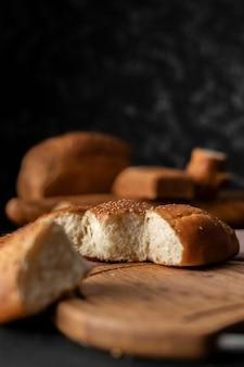 Świeżo upieczona miękka słodko podzielona bułka z sezamem na niej, oderwana od chleba
