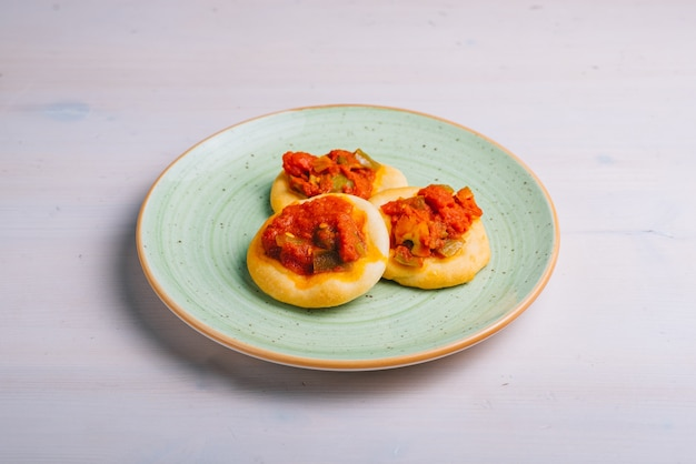 Świeżo upieczona mini pizza z pomidorami i warzywami. tradycyjne hiszpańskie ciasto z warzywami.