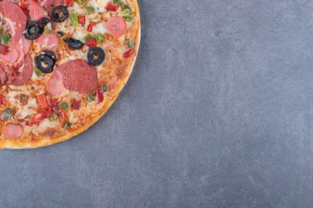Świeżo upieczona pizza pepperoni na szarym tle.