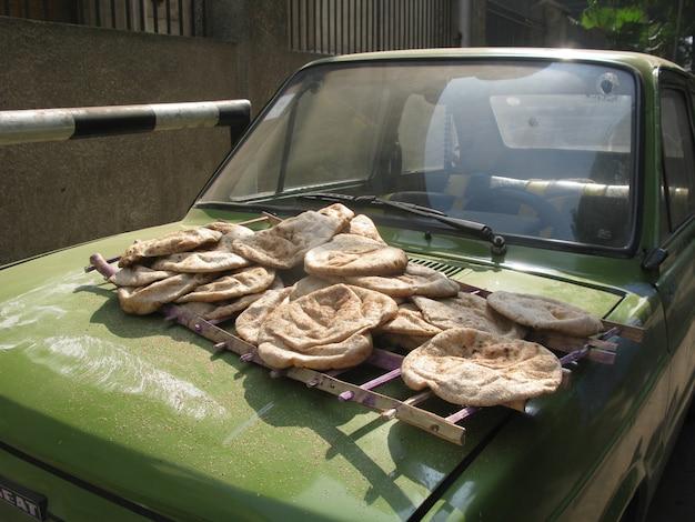 Świeżo upieczone bochenki egipskich podpłomyków na sprzedaż z przodu zielonego samochodu na ulicy