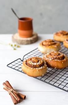 Świeżo upieczone bułeczki cynamonowe z przyprawami na drewnianym tle. kanelbule - szwedzki deser. koncepcja żywności. styl rustykalny