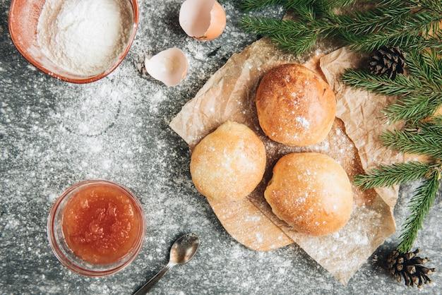 Świeżo upieczone bułeczki drożdżowe wypełnione dżemem jabłkowym na szarym tle z mąki.
