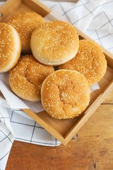 Świeżo upieczone bułeczki hamburgerowe leżą na drewnianej tacy na stole z białą serwetką. ciastka o smaku żółtym z białym sezamem.