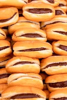 Świeżo upieczone bułeczki z nadzieniem czekoladowym lub kremem nugatowym na włoskim niedzielnym targu spożywczym. hot dog z czekoladą