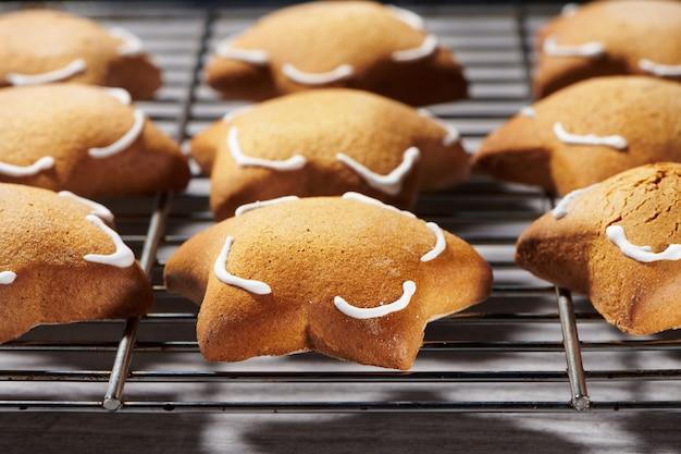 Świeżo upieczone ciasteczka imbirowe w kształcie gwiazdy na stojaku do chłodzenia. zbliżenie selektywnej ostrości widoku.