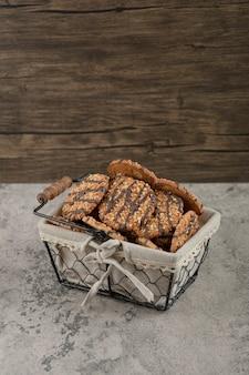 Świeżo upieczone ciasteczka wieloziarniste z polewą czekoladową w koszyku.