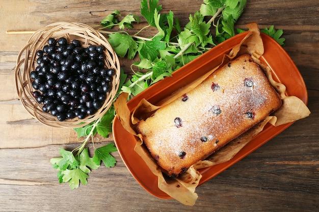 Świeżo upieczone ciasto z czarnych porzeczek w brązowej patelni na drewnianym stole, widok z góry