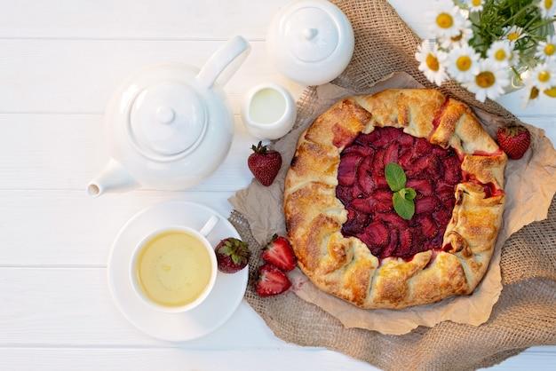 Świeżo upieczone domowe ciasto truskawkowe galette, filiżanka herbaty, imbryk i wazon z bukietem stokrotek.