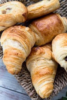 Świeżo upieczone francuskie wypieki z masłem w koszyku. rogaliki, biszkopt, czekolada rodzynki