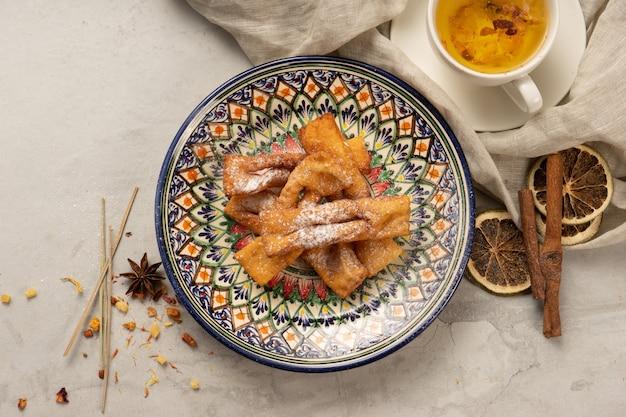 Świeżo upieczone herbatniki z chrustu z cukrem pudrem w ozdobnym narodowym uzbeckim talerzu ceramicznym z tradycyjnym wzorem. słodkie wypieki na deser na herbatę