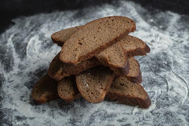 Świeżo upieczone kromki ciemnego chleba na tle białej mąki.