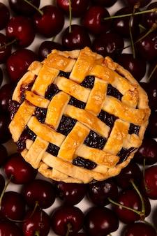 Świeżo upieczone mini ciasto wiśniowe to jesienny domowy posiłek na tle dojrzałych wiśni