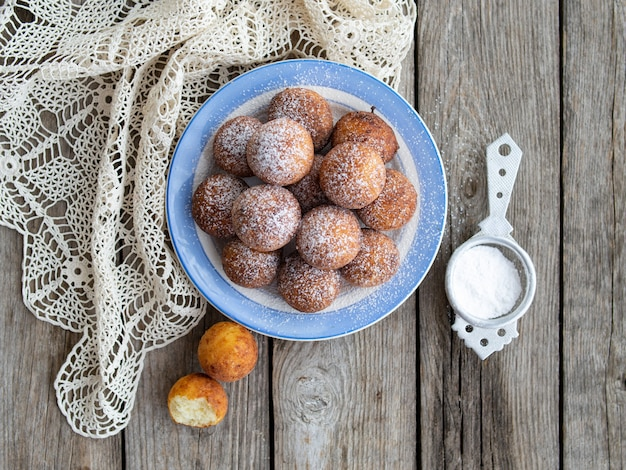 Świeżo upieczone pączki z serem z cukrem pudrem na talerzu na drewnianym stole rustykalnym. atmosfera przytulnego domowego śniadania. zamknij się, skopiuj miejsce.