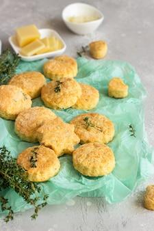 Świeżo upieczone pyszne angielskie bułeczki lub ciasteczka z serem i tymiankiem. pikantne bułeczki z serem lub ciastka.