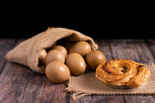 Świeżo upieczone rogaliki z jajkami w worku na drewnianym stole