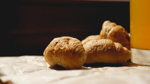 Świeżo upieczone rogaliki z sokiem pomarańczowym na papierze pakowym. fotografia zbliżenie świeżego pysznego deseru na śniadanie.